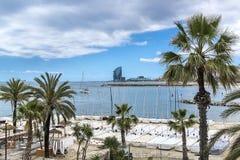 La playa de Barcelona con las palmeras y los yates Fotos de archivo libres de regalías