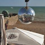 La playa de Brighton reflejó en una ejecución de la bola de espejo en uno de los cafés del frente de la playa Imagenes de archivo