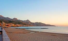 La playa de la salida del sol en el centro turístico de Giardini Naxos Fotos de archivo