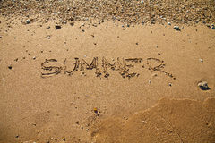 La playa de Sandy agita en la inscripción del verano del mar de la puesta del sol en la arena Fotos de archivo