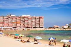 La playa de Sunny Mediterranean, turistas se relaja en la arena, gente se baña Foto de archivo
