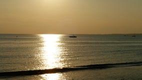 La playa en la puesta del sol, barco de pesca lejos Fotografía de archivo libre de regalías