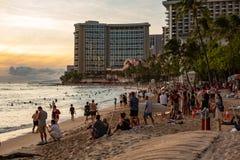 La playa icónica de Waikiki en la puesta del sol con una muchedumbre de apprec de la gente imagen de archivo