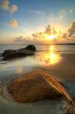 La playa mientras que va el sol abajo Foto de archivo libre de regalías