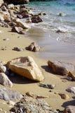 La playa perfecta con la arena hermosa, las piedras y la agua de mar clara imagen de archivo