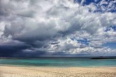 La playa soleada, las nubes oscuras y la turquesa riegan Isla del paraíso, Bahamas Imagen de archivo libre de regalías