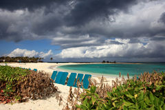 La playa soleada, las nubes oscuras y la turquesa riegan Isla del paraíso, Bahamas Imagen de archivo