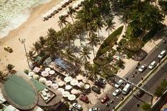 La playa tropical con las palmas y el tráfico por carretera de la ciudad pone en contraste foto de archivo