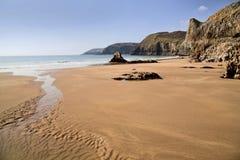 La playa y Rocky Layered Coastline de Sandy de la Virgen entre Lydstep y Manorbier aúllan foto de archivo