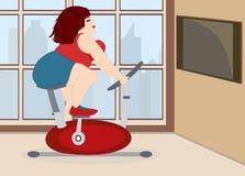 La pleine fille mignonne est engagée sur un vélo d'exercice à la maison Image libre de droits