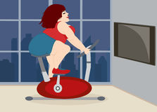 La pleine fille mignonne est engagée sur un vélo d'exercice à la maison Photo libre de droits