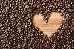 La pleine image de cadre de l'obscurité fraîche a rôti des grains de café avec l'espace de copie de forme d'amour Images stock
