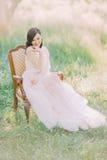 La pleine-lenght photo de la femme de sourire dans la longue robe blanche se reposant sur la vieille chaise moderne dans le domai Photos stock