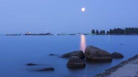La pleine lune la nuit blancs assaisonnent au-dessus du lac en Carélie Image stock