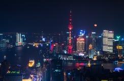 La pleine lune se lève derrière l'horizon de Pudong Photographie stock libre de droits