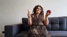 La pleine robe de fille repose des vacances sur le régime bien choisi alternatif de gâteau aux pommes de divan banque de vidéos
