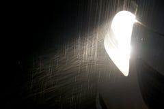 La pluie a affecté le phare léger de voiture dans l'obscurité Photographie stock