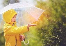 La pluie contagieuse d'enfant heureux laisse tomber au printemps le parc image stock