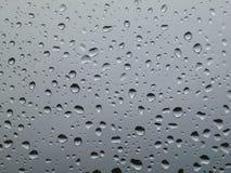 La pluie de photo de fond sur le verre Photographie stock