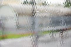 La pluie sur la fenêtre avec le fond brouillé Image stock