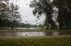 La pluie tombe sur le verre de fenêtre Fond photographie stock libre de droits