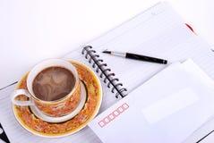 La pluma, café y envuelve en el cuaderno Imagen de archivo