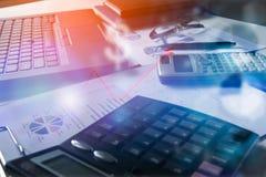 La pluma con los gráficos de negocio y las cartas divulgan, calculadora en el escritorio del cepillado financiero Imagenes de archivo