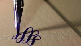 La pluma de la tinta escribe en las líneas de papel primer del vintage almacen de metraje de vídeo
