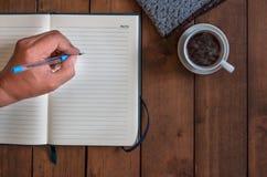La pluma de tenencia de la mano escribe en el cuaderno con la taza de café en de madera Fotos de archivo