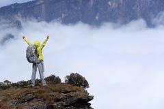La pluma del caminante de la mujer joven arma en pico de montaña Foto de archivo