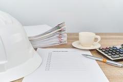 La pluma en lista de control tiene el sombrero y café del ingeniero como fondo Fotografía de archivo libre de regalías