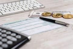 La pluma, los bitcoins, los billetes de dólar y la calculadora en la forma de impuesto U 1040 S al lado del teclado de ordenador  imagenes de archivo
