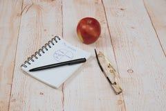 La pluma, los vidrios y el cuaderno están en la tabla Fotografía de archivo libre de regalías
