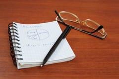La pluma, los vidrios y el cuaderno están en la tabla Foto de archivo