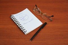 La pluma, los vidrios y el cuaderno están en la tabla Imagen de archivo libre de regalías