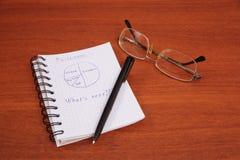 La pluma, los vidrios y el cuaderno están en la tabla Imagen de archivo