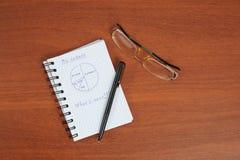 La pluma, los vidrios y el cuaderno están en la tabla Fotos de archivo libres de regalías