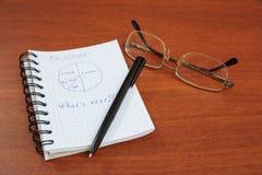La pluma, los vidrios y el cuaderno están en la tabla Imágenes de archivo libres de regalías