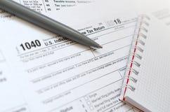 La pluma y el cuaderno es mentiras en la forma de impuesto U 1040 S Individua fotografía de archivo libre de regalías
