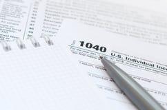 La pluma y el cuaderno es mentiras en la forma de impuesto U 1040 S Individua Fotos de archivo libres de regalías