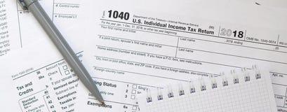 La pluma y el cuaderno es mentiras en la forma de impuesto U 1040 S Individua Imagen de archivo
