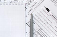 La pluma y el cuaderno es mentiras en la forma de impuesto U 1040 S Individua Imágenes de archivo libres de regalías