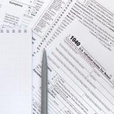 La pluma y el cuaderno es mentiras en la forma de impuesto U 1040 S Individua Foto de archivo