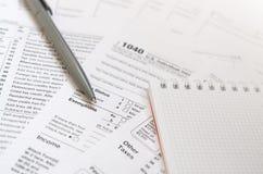 La pluma y el cuaderno es mentiras en la forma de impuesto U 1040 S Individua Imagen de archivo libre de regalías