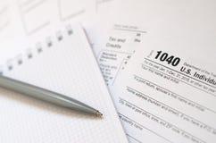La pluma y el cuaderno es mentiras en la forma de impuesto U 1040 S Individua Foto de archivo libre de regalías