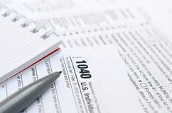 La pluma y el cuaderno es mentiras en la forma de impuesto U 1040 S Individua Fotografía de archivo
