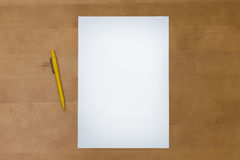 La pluma y el papel en blanco cubren en una tabla de madera Fotografía de archivo