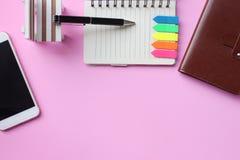 La pluma y el smartphone del cuaderno se colocan en un piso rosado y tienen foto de archivo
