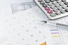 La pluma y la calculadora colocadas en la reunión planean en calendario Fotografía de archivo