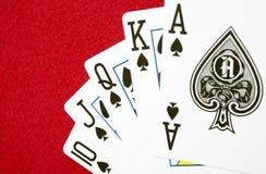 La plus grande main en jeu de poker sur le fond rouge Image stock
